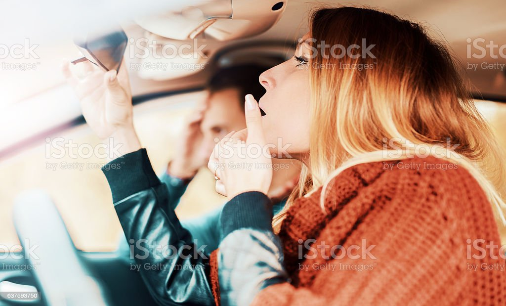 Woman watching her makeup in the mirror while driving a - foto de acervo
