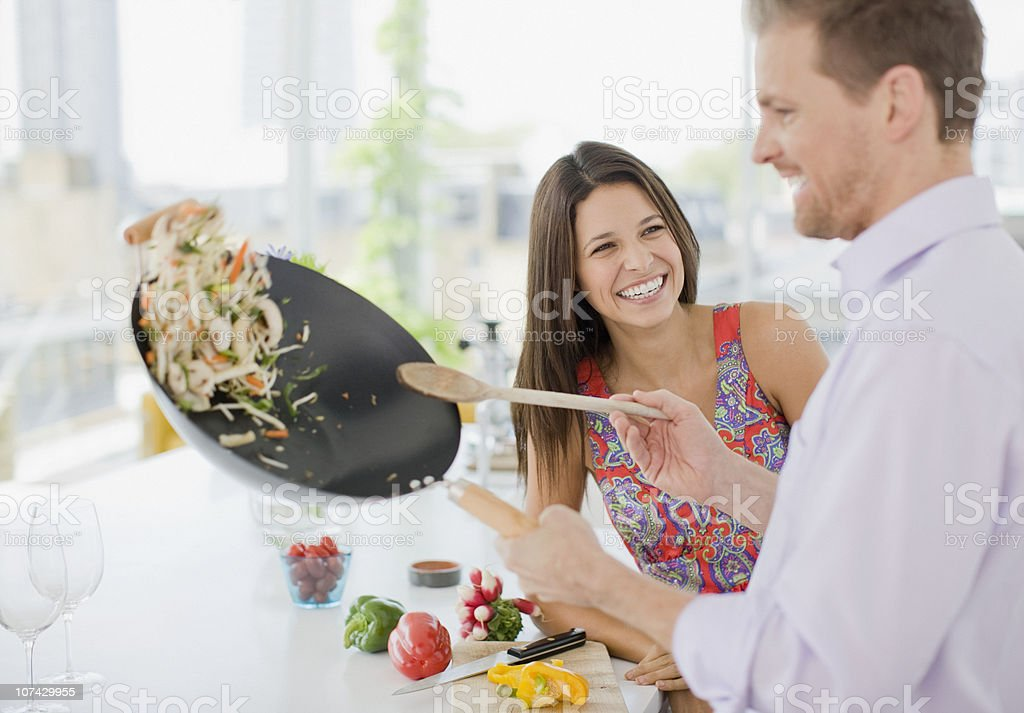 Woman watching husband flipping stirfry in the kitchen stock photo