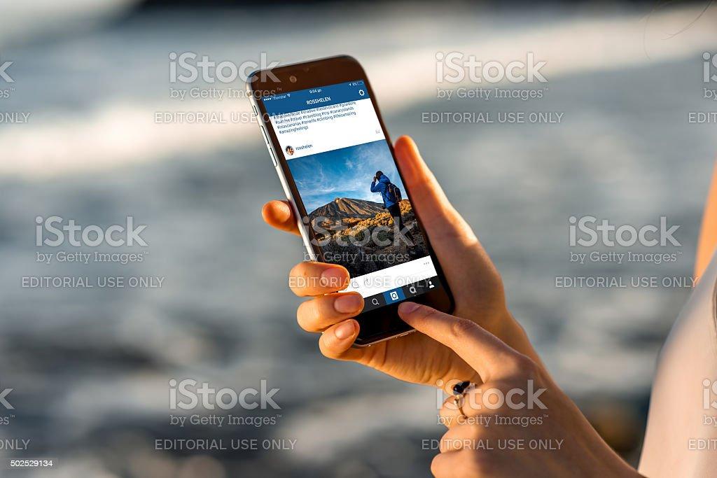 Donna guardando foto su Instagram notizie con il nuovo iPhone - foto stock