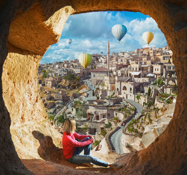 Woman watching  like colorful hot air balloons flying over the valley at Cappadocia stock photo