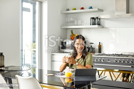 Smiling female watching movie on digital tablet. Young woman in casuals is enjoying coffee during breakfast. She is sitting at dining table in house.