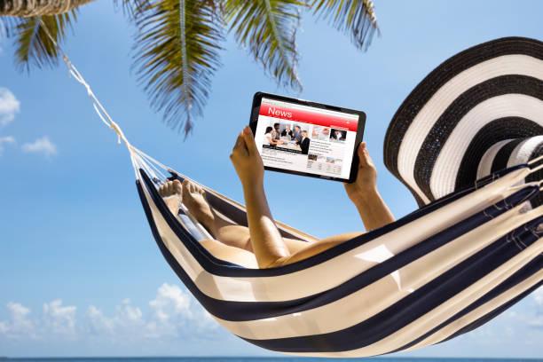vrouw kijken nieuws op digitale tablet tegen blue sky - newspaper beach stockfoto's en -beelden