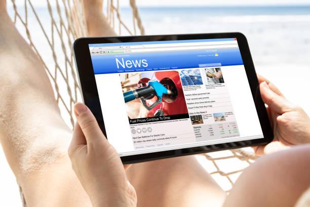 vrouw kijken nieuws op digitale tablet op het strand - newspaper beach stockfoto's en -beelden