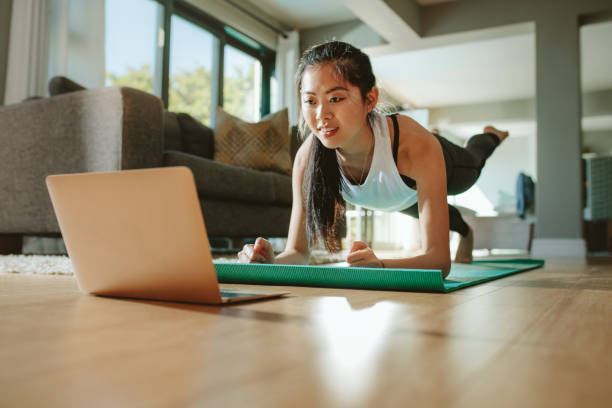 Woman watching sport training online on tablet Woman working out at home watching video tutorial on laptop. Fit young woman in plank position repeating online instructions by coach on computer. jacoblund stock pictures, royalty-free photos & images