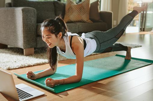 Woman Watching Sports Training Online On Laptop - Fotografie stock e altre immagini di Adulto