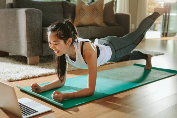 Woman watching sports training online on laptop. Smiling woman exercising at home and watching training videos on laptop. Chinese female doing planks with a leg outstretched and looking at laptop. exercising stock pictures, royalty-free photos & images