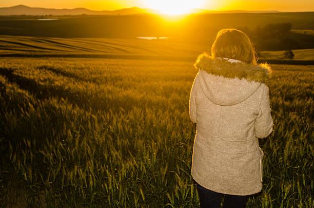 Woman watching sunset stock photo