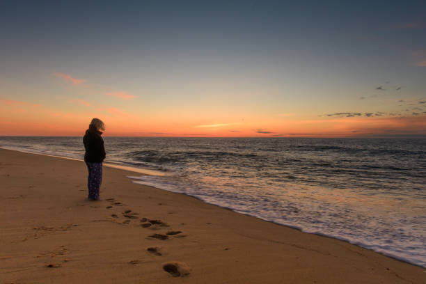 Woman watching the sunrise at the beach stock photo