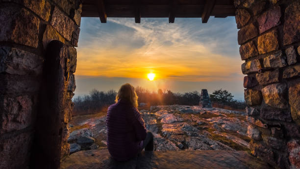 Woman watching the sunset along the Appalachian Trail in Stokes State Forest, New Jersey Relaxing photo watching the sunset on the Appalachian Trail appalachian trail stock pictures, royalty-free photos & images
