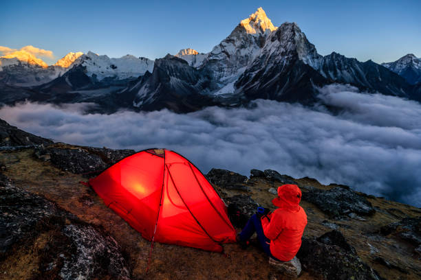 Woman watching the sunset over Himalayas, Everest Region stock photo
