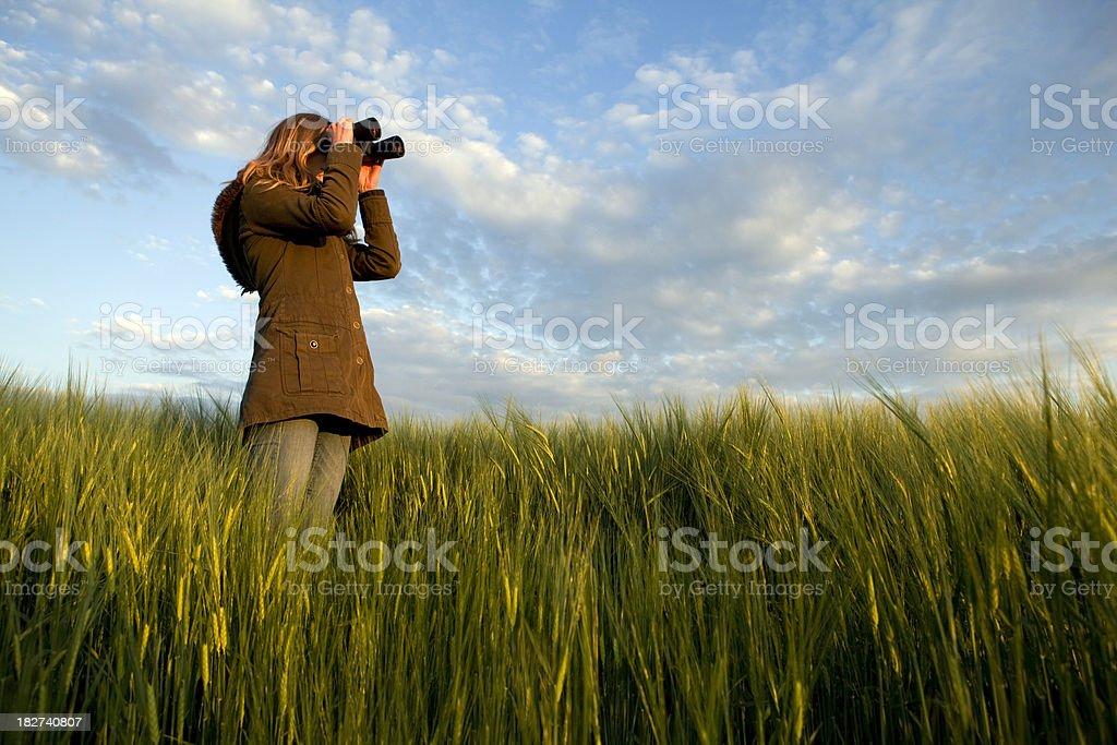 Woman watching thru binoculars stock photo