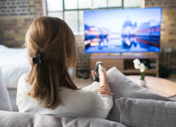 Woman watching tv at home Woman relaxing at home watching tv and holding the remote control one mid adult woman only stock pictures, royalty-free photos & images