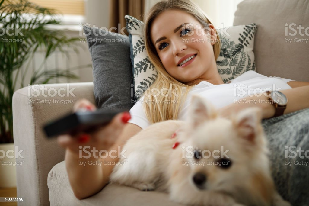 Woman watching TV at home stock photo