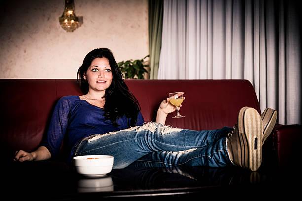 donna guardando la tv a notte - divano procrastinazione foto e immagini stock