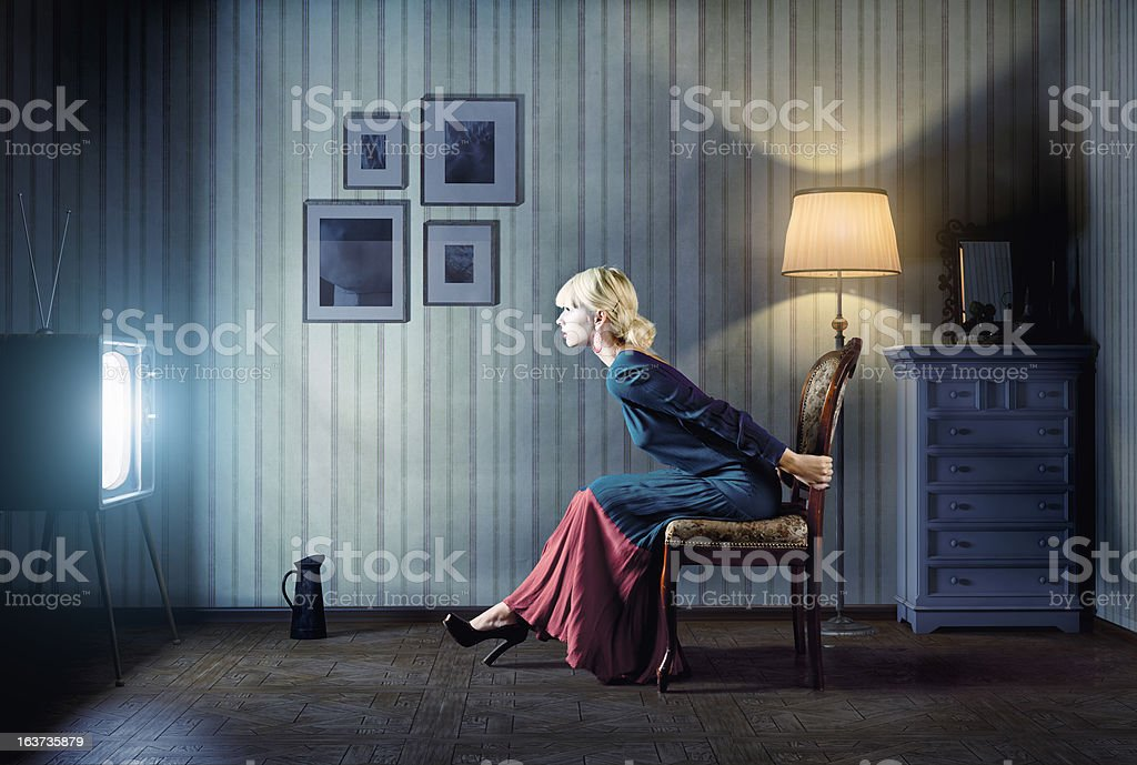 Woman watching TV in blue dress stock photo