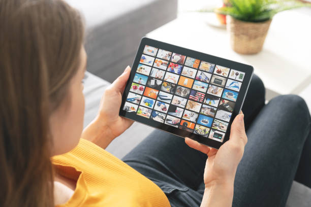 Woman watching TV on tablet. Multimedia services stock photo