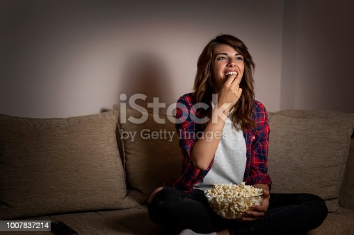Beautiful young woman sitting in the dark on a living room couch, having fun watching TV and eating popcorn