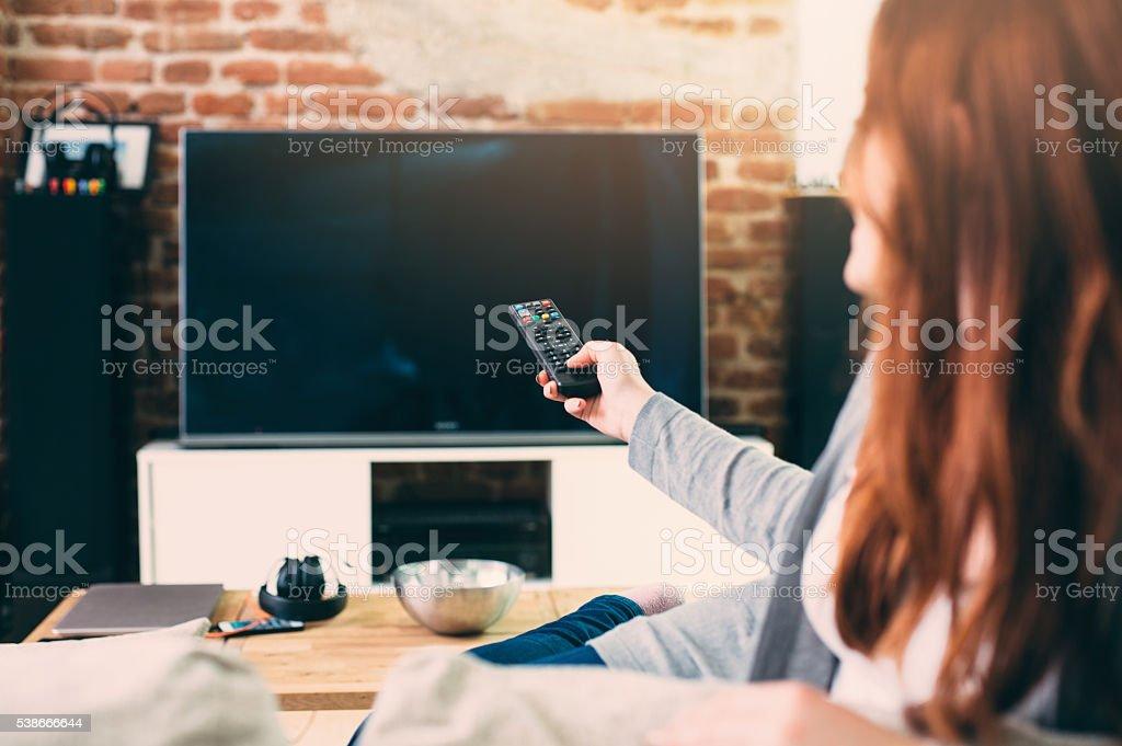 Mulher assistindo TV - foto de acervo