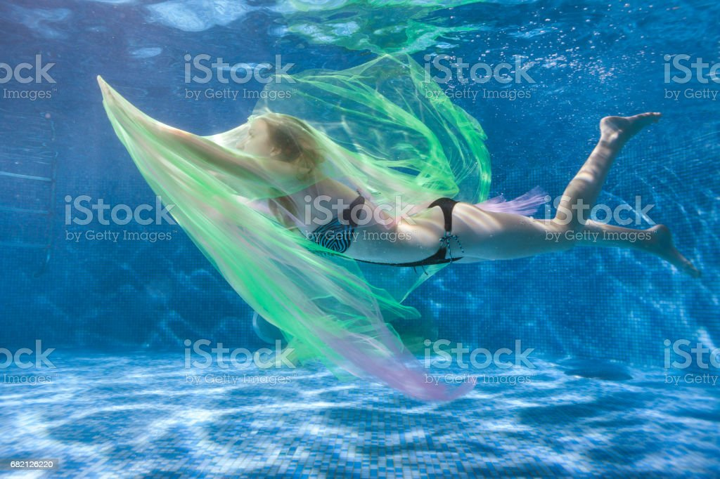 Woman water plays with a transparent fabric. stock photo