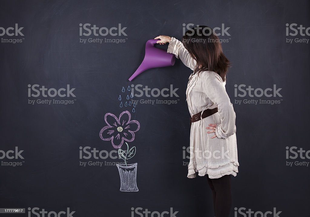 Woman watering a drawing plant royalty-free stock photo