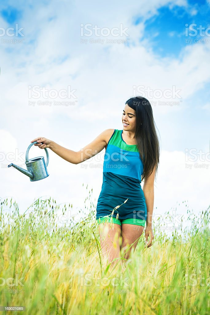 Woman watering a green field royalty-free stock photo