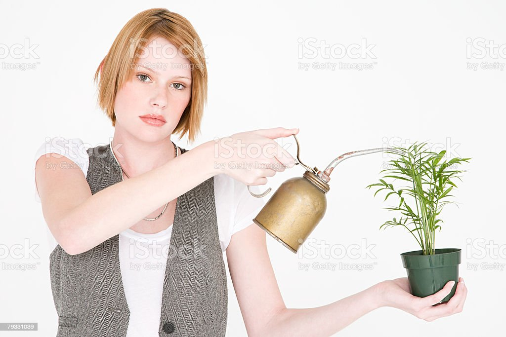 A woman watering a plant with a jerry can royalty-free 스톡 사진