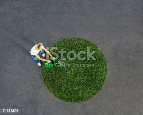 istock Woman watering circle of grass on pavement 74181324