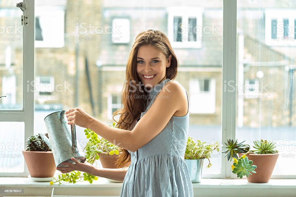 Woman watering plants Beautiful young woman watering potted plants at her home, smiling at camera. 20-24 Years Stock Photo