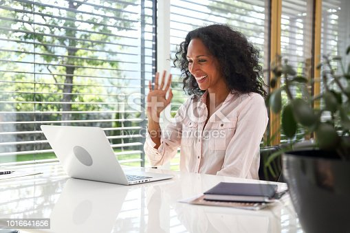 Mid-adult woman at home greeting her caller with video conference call. Nice home office space.