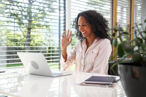 Frau winkt Laptop in der Mitte eines videokonferenzgesprächs – Foto