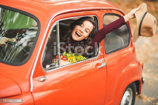 Happy woman carrying groceries bag and waving from her old timer car