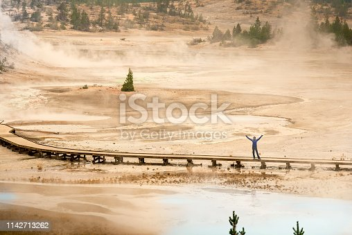 Woman viewed from afar standing on the boardwalk and waving with open arms at Norris Geyser Basin.