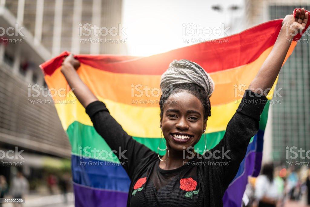 Woman Waving Rainbow Flag at Gay Parade stock photo