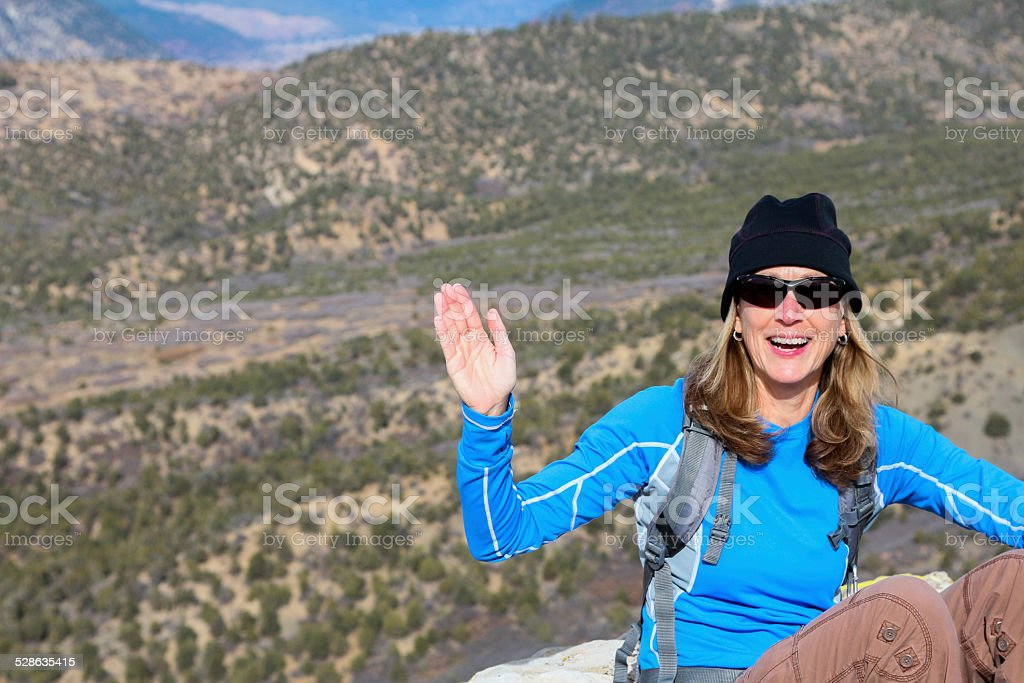 Woman Waving to the Camera from an Overlook stock photo