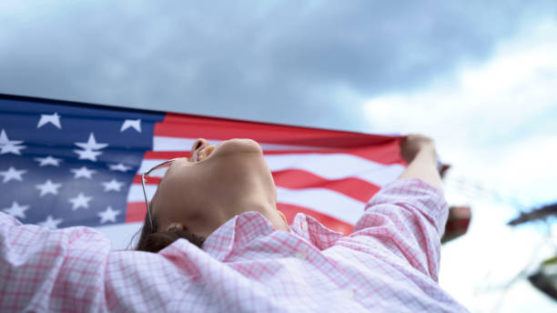 Woman waving US flag, patriot, secure future for young people in their country Woman waving US flag, patriot, secure future for young people in their country citizenship stock pictures, royalty-free photos & images