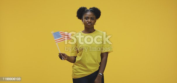 Medium shot of a young woman waving the flag of the United States