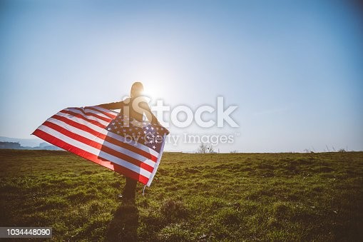 Young red haired woman carrying flag of the United States of America