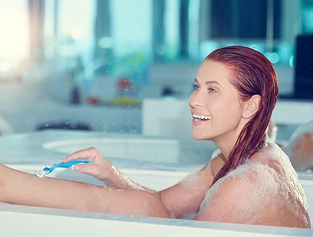 woman waxing inside bathtub - feminine badezimmer stock-fotos und bilder