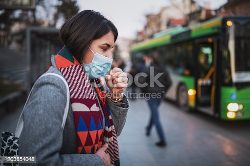 Side view of woman wear face mask and coughing while standing in the town, looking down