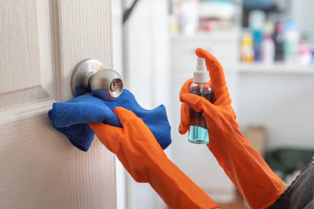 Woman wear orange rubber gloves cleaning door, doorknob with alcohol spray at the house. stock photo