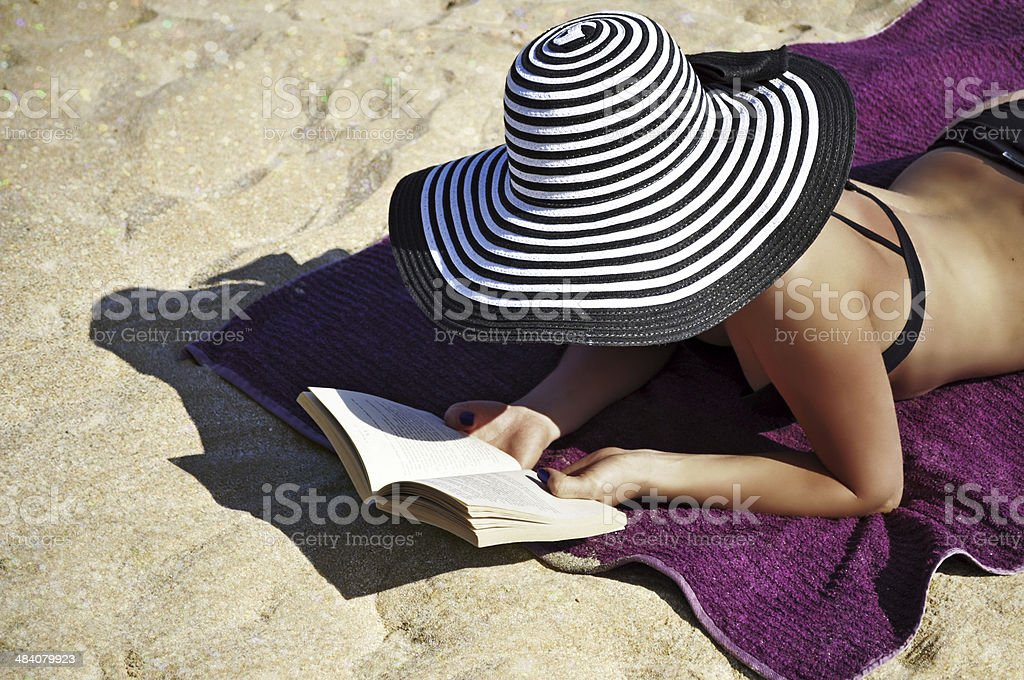 Woman wearing a big summer hat reading on the beach. - Royalty-free Adult Stock Photo