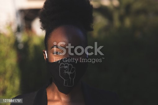Woman wearing a black face mask with a fist printed on it, protesting for human rights of black people.