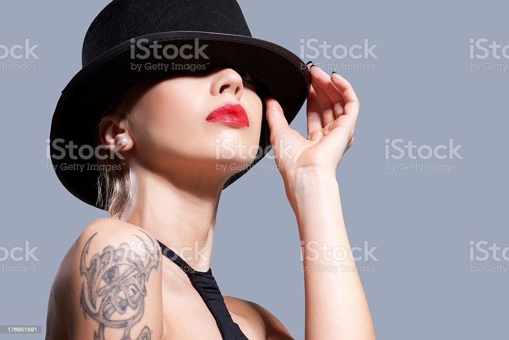 Woman wearing a black hat with a tattoo on her arm stock photo