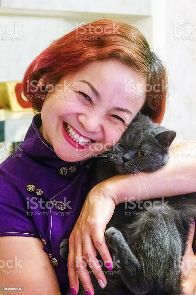 Woman wearing a cheongsam holding a black cat is laughing. stock photo