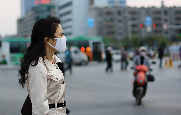 woman wearing a face mask against pollution or disease - virus stock pictures, royalty-free photos & images