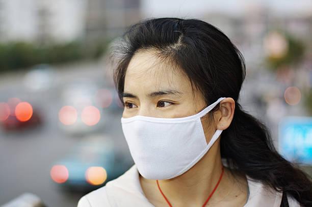donna che indossa una maschera di protezione contro l'inquinamento o malattia - febbre russa foto e immagini stock