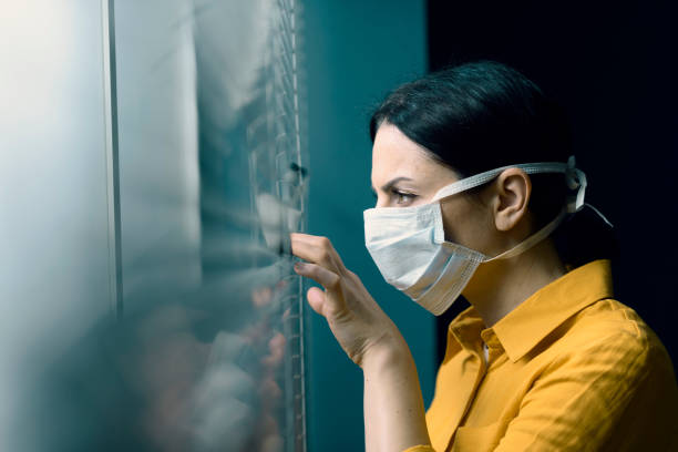 Woman wearing a face mask and peeking out from blinds