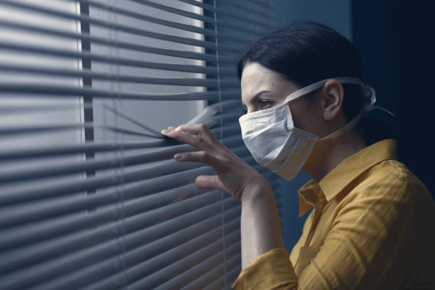 Woman wearing a face mask and peeking out from blinds Suspicious woman wearing a face mask and peeking outside, covid-19 outbreak and virus infection concept biological process stock pictures, royalty-free photos & images