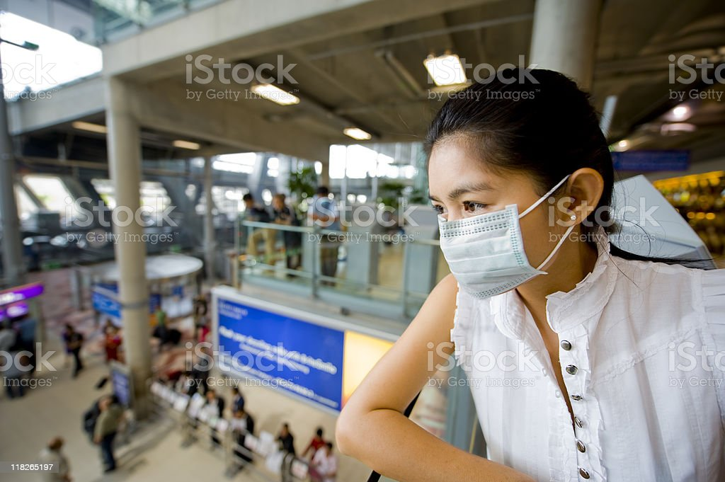 Woman wearing a face mask at the airport stock photo
