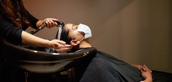 Young woman wearing a protective face mask getting her hair washed by a hairdresser in a salon